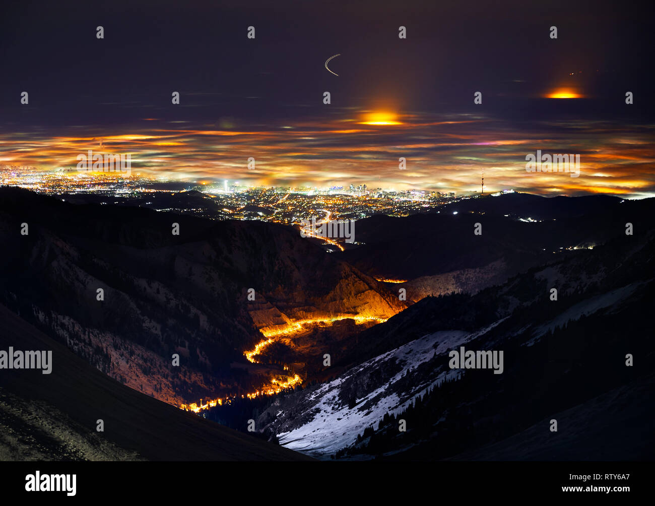 Almaty city lights at foggy winter night view from the mountains, Kazakhstan, Central Asia. Stock Photo