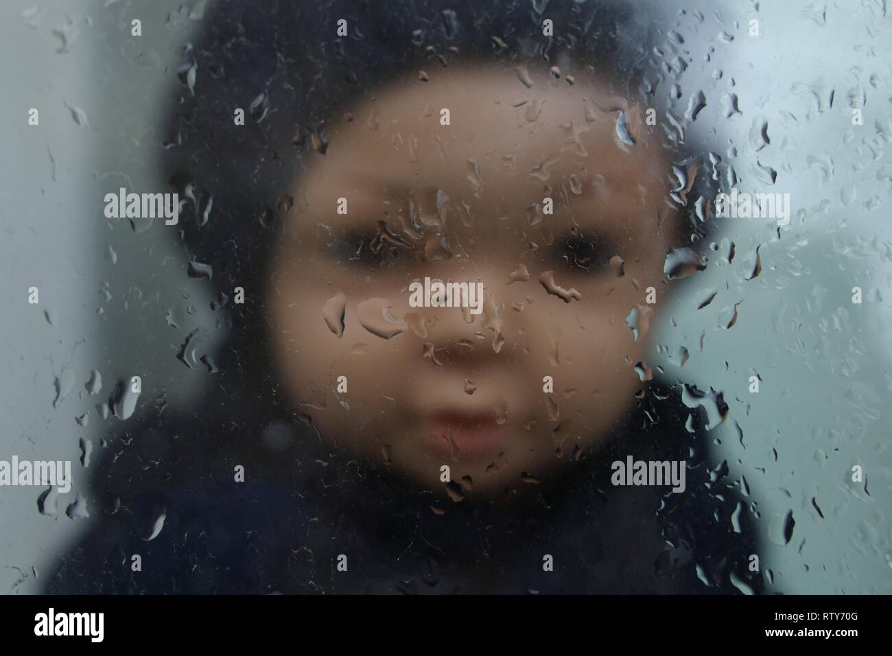 children's doll in a black hat in the out-of-focus, behind the glass, wet from the rain - Stock Image