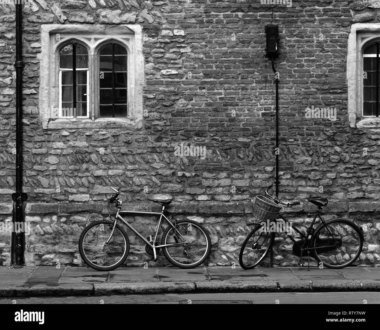 Two bicycles against the wall of Trinity College Cambridge England - Stock Image
