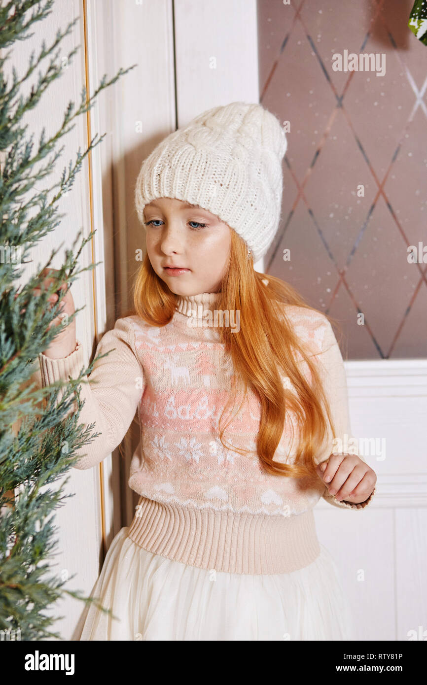 daee0bd76 Bright red-haired little girl in a white hat and a beautiful dress is  sitting in an autumn cafe. Redhead girl with big blue eyes and a beautiful  sweat