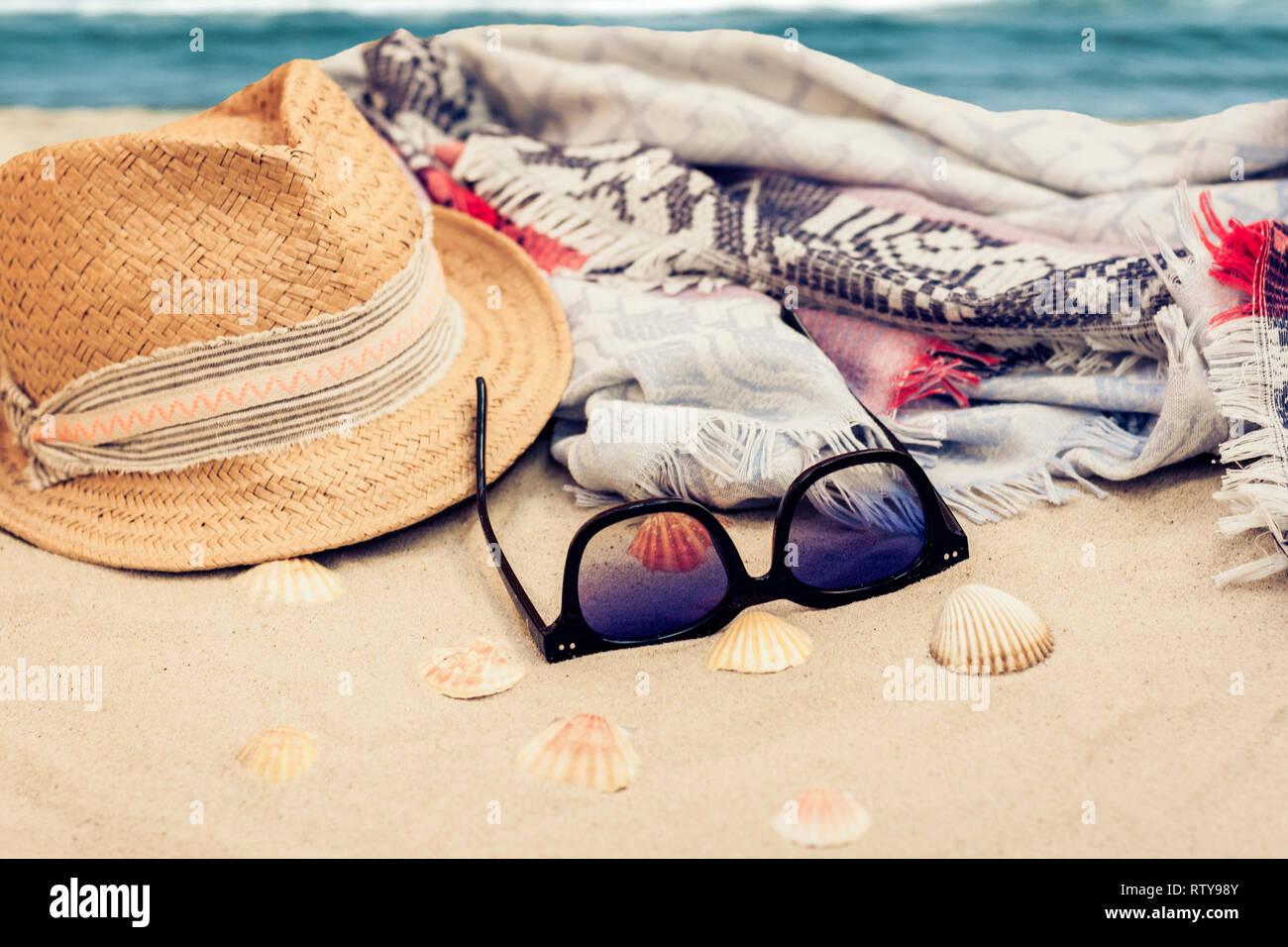 94dfd87c Straw hat, cover-up beachwear wrap and sun glasses on a tropical beach -