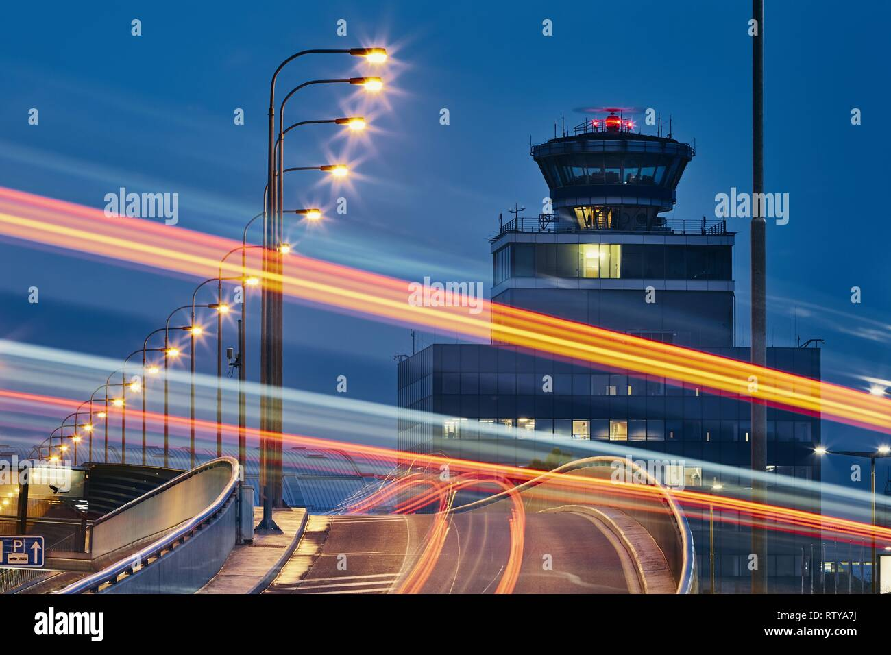 Light trails of the cars on the road to airport against air traffic control tower. Stock Photo