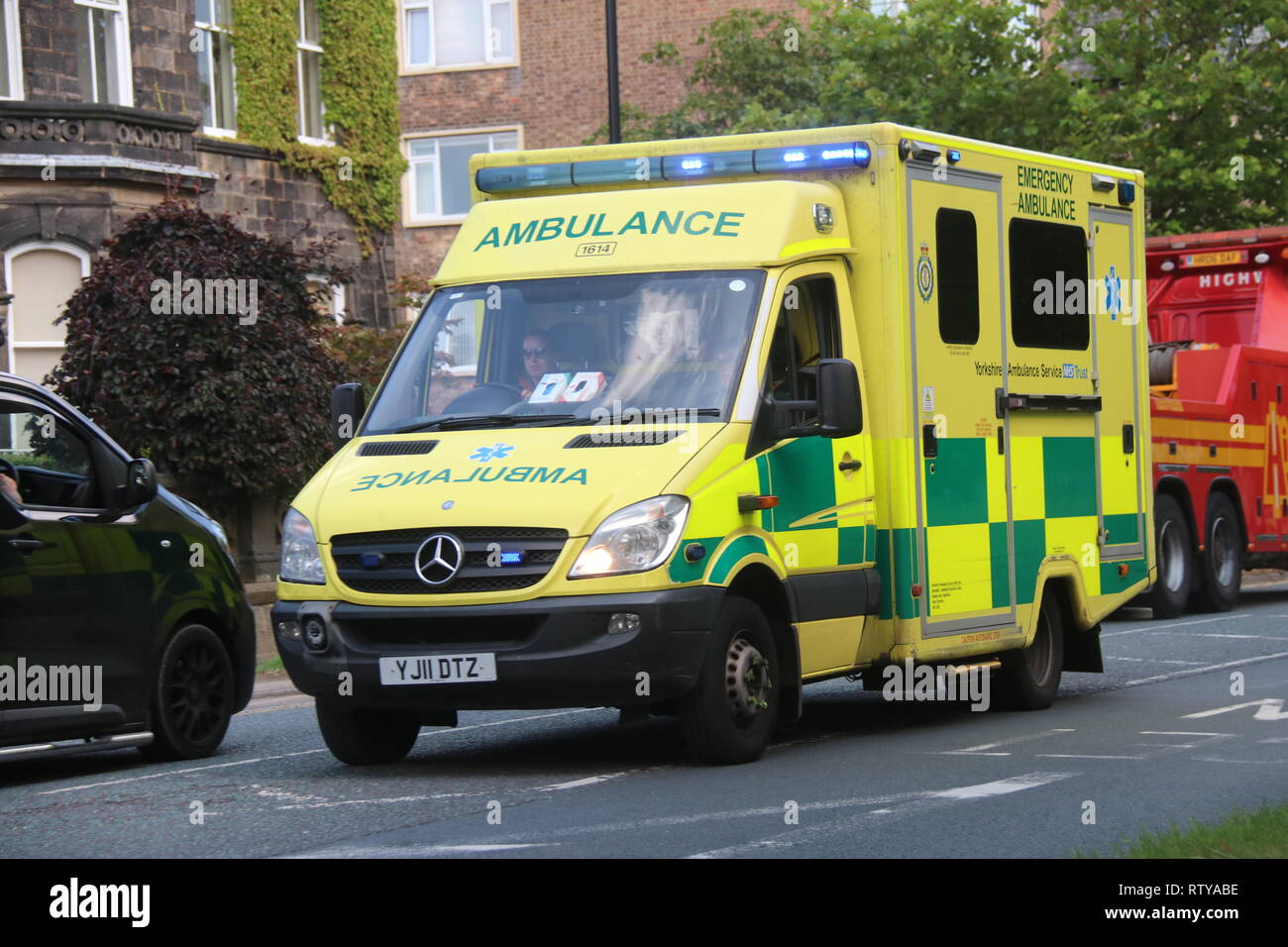 A YORKSHIRE AMBULANCE WITH BLUE LIGHTS FLASHING ON A BUSY STREET - Stock Image