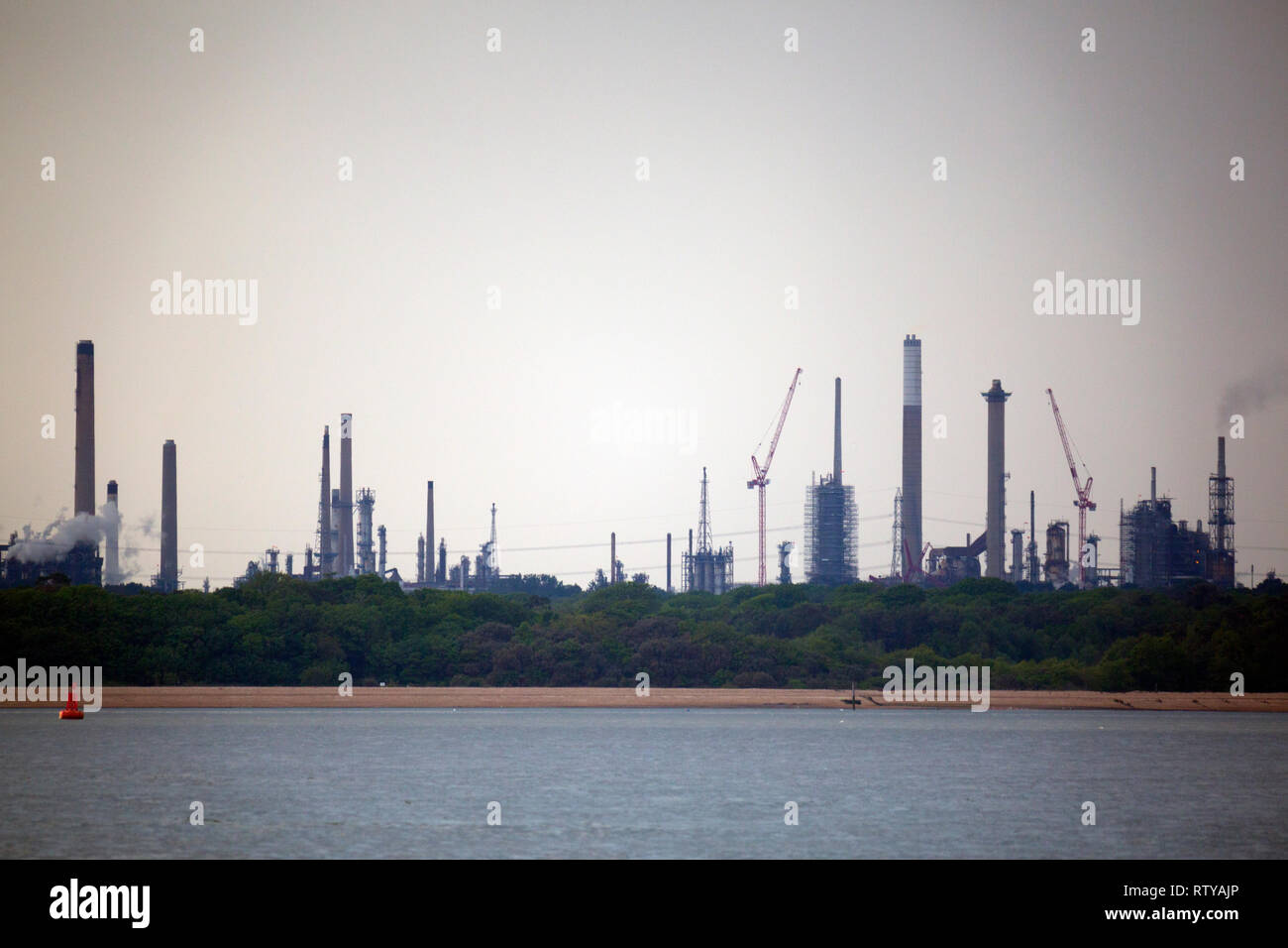 The Solent, Fawley,oil,refinery, cracking,towers,cranes,chimney,chimneys,flames, New Forest,Hampshire, Isle of Wight, England, UK, silhouette, - Stock Image