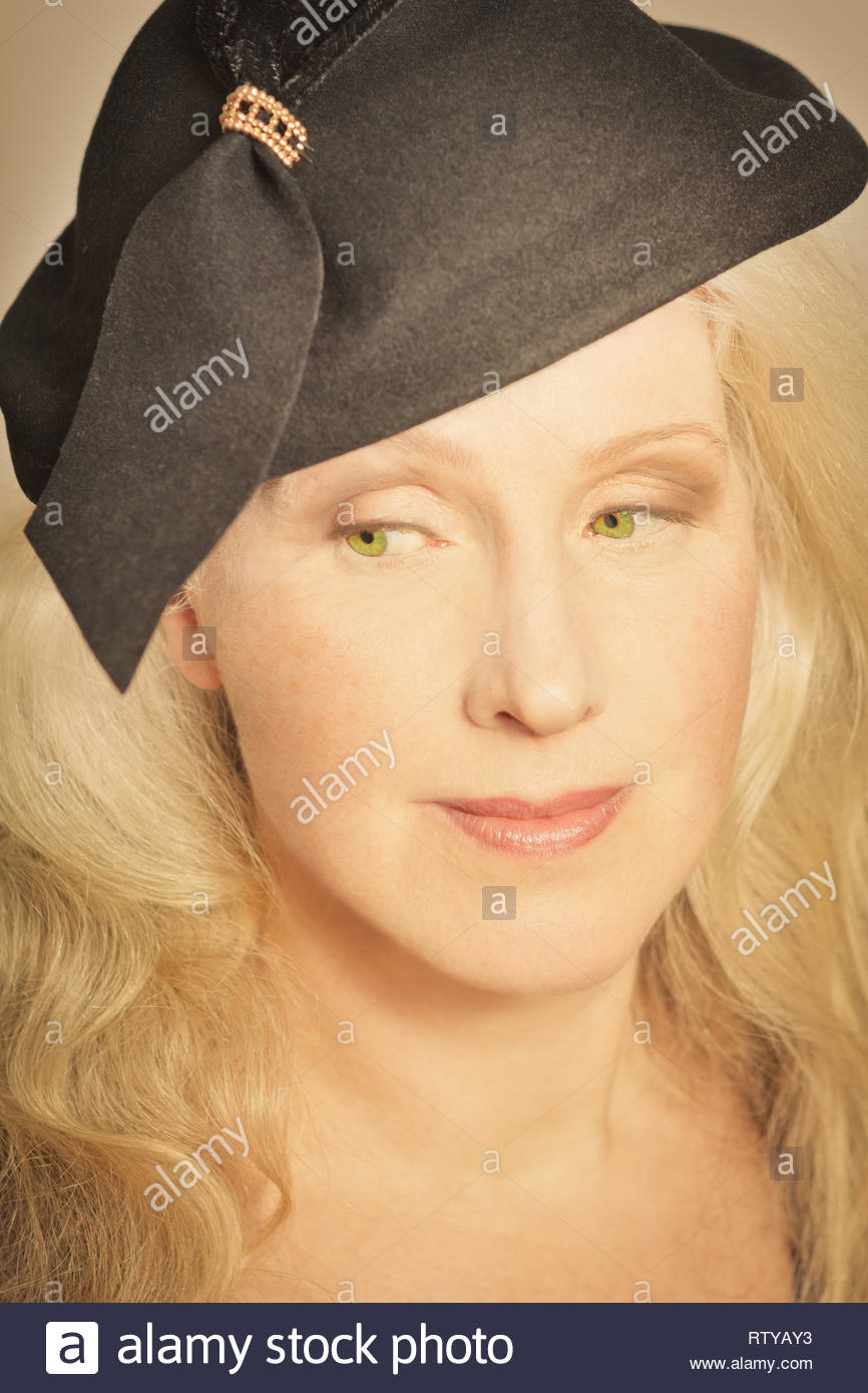 Closeup portrait of beautiful mature woman with long hair and vintage hat, faded retro filter effect. Stock Photo