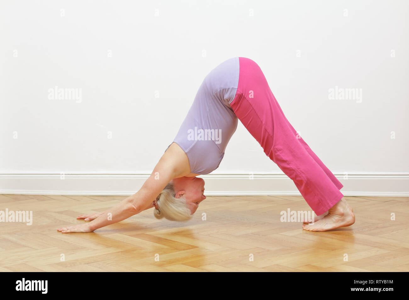 Senior woman with gray hair doing yoga exercise at home in front of a white wall, asana downward dog Stock Photo