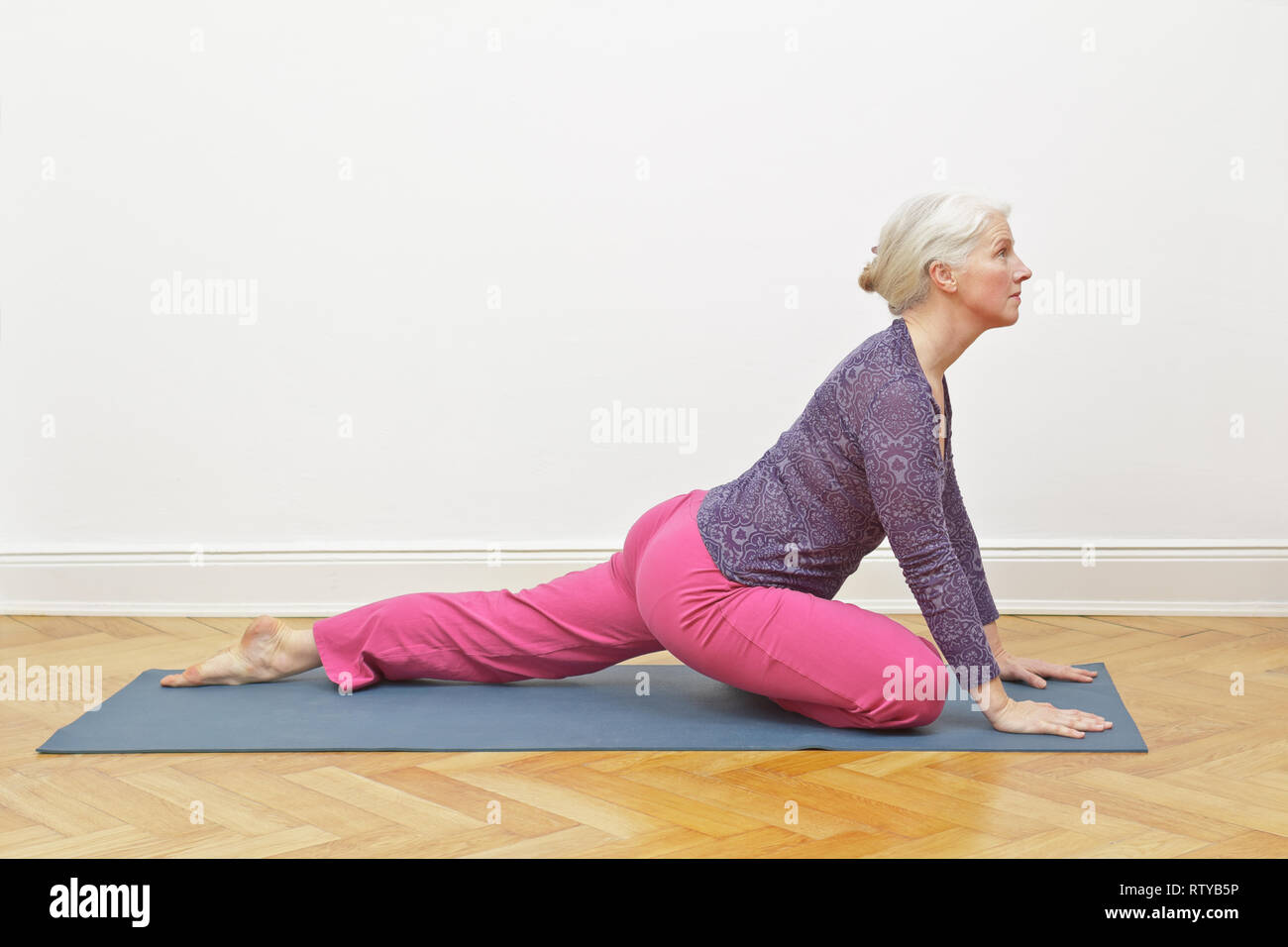 Senior woman with gray hair exercising yoga at home on a mat in front of a white wall, asana pigeon intro Stock Photo