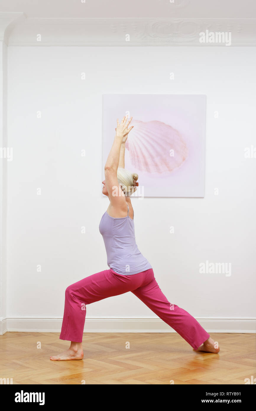 Senior woman with gray hair doing yoga exercises at home in front of a wall with a picture, asana warrior I Stock Photo