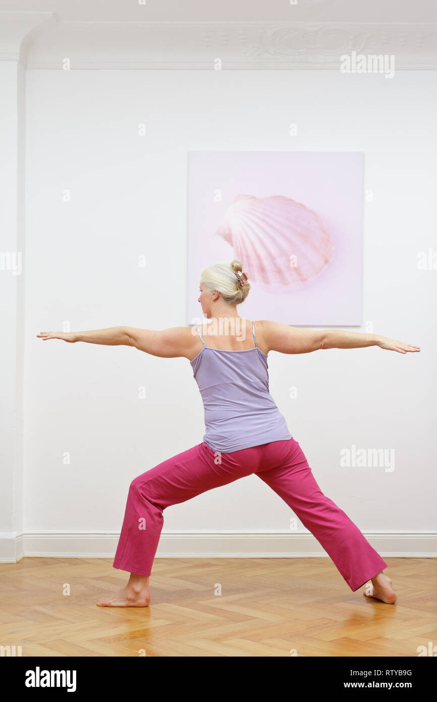 Senior woman with gray hair doing yoga exercises at home in front of a wall with a picture, asana warrior II Stock Photo