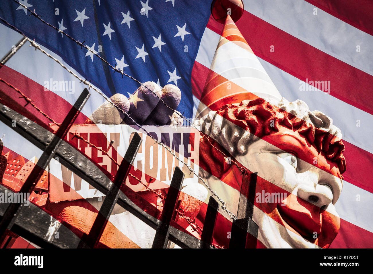 Clown holding welcome sign behind razor wire fence: USA, United States of America immigration concept image. - Stock Image
