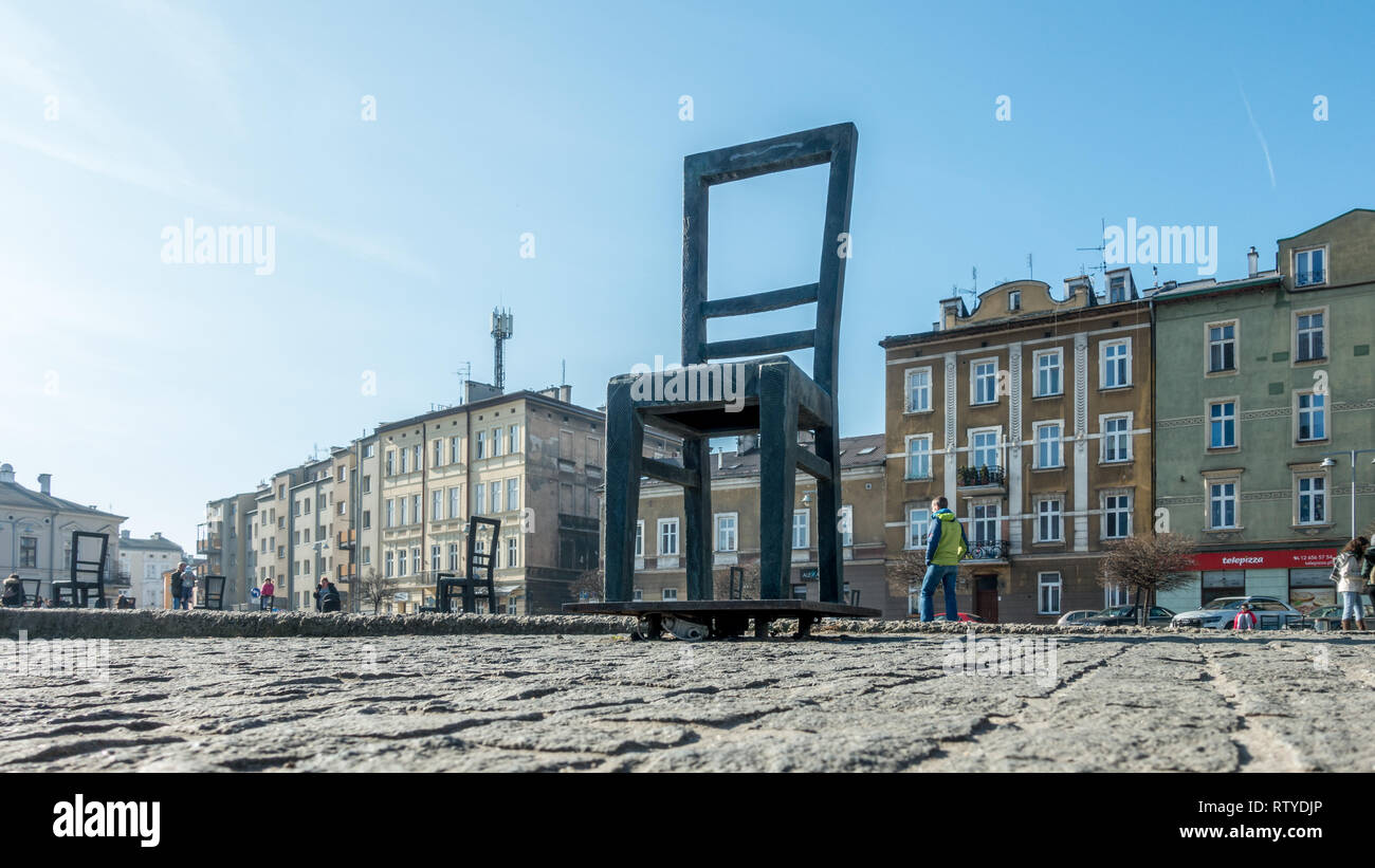 People studying a map at the metal chairs in memory of the jewish people killed on the Ghetto Heroes Square, Krakow, Poland Stock Photo