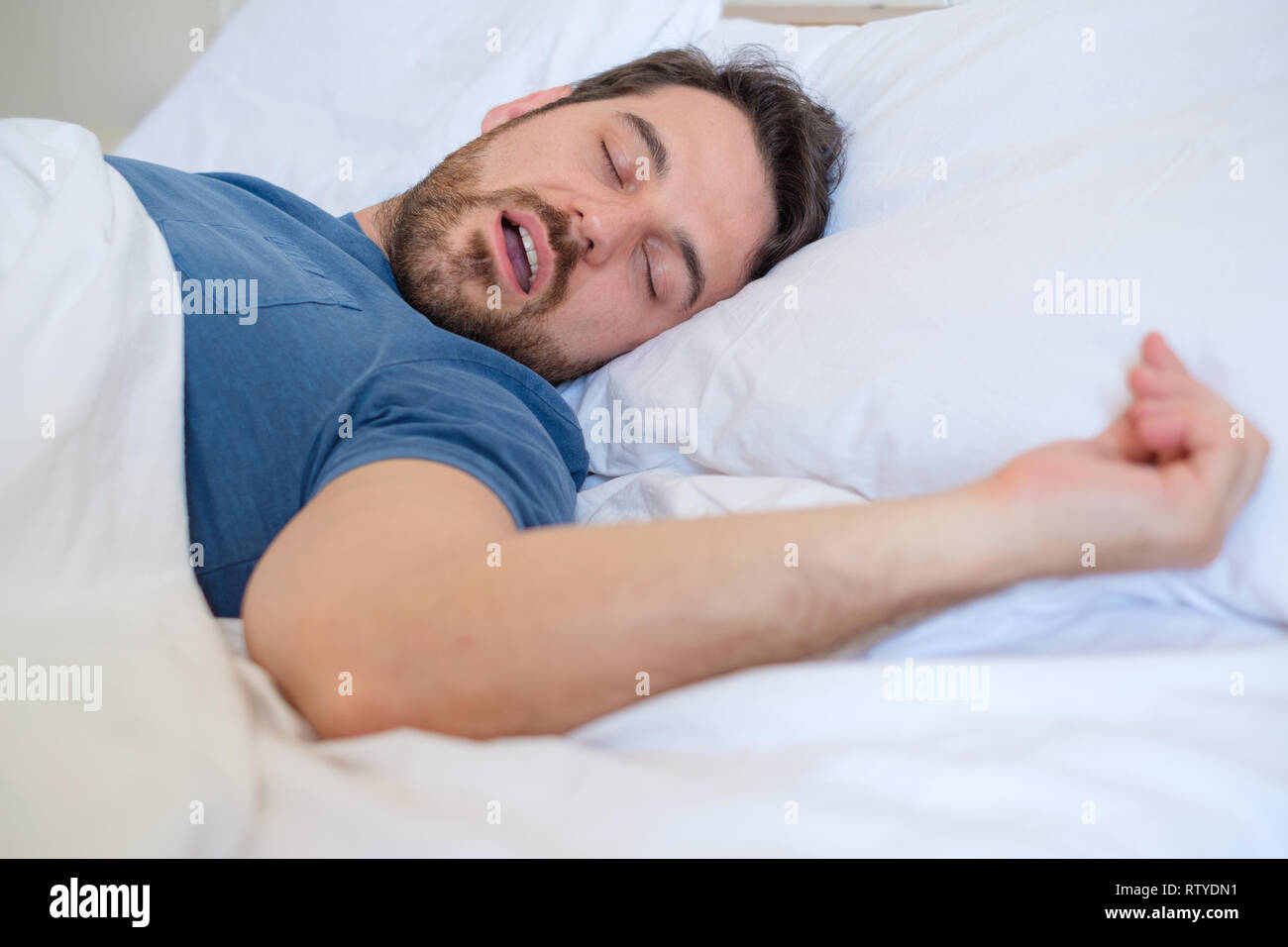 Tired man sleeping and snoring loudly in the bed - Stock Image