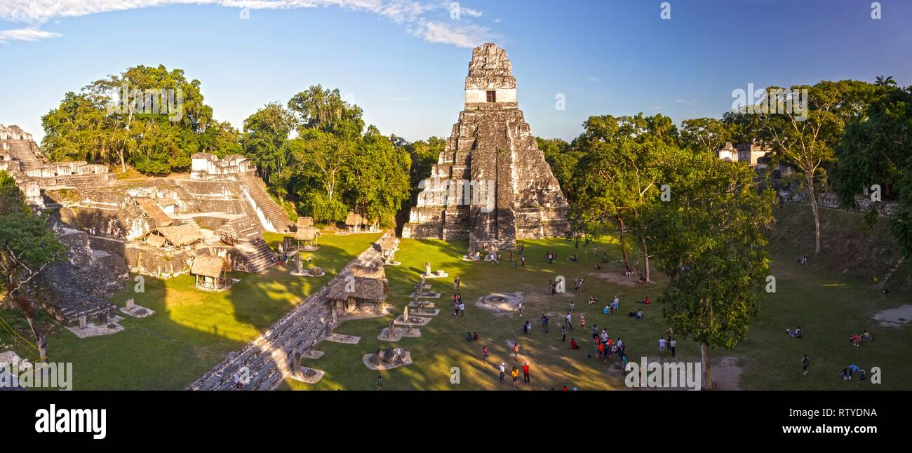 Panoramic Aerial View of Tourists in Grand Plaza surrounded by Ancient Mayan Citadels and Temple Ruins in Tikal National Park, Guatemala - Stock Image