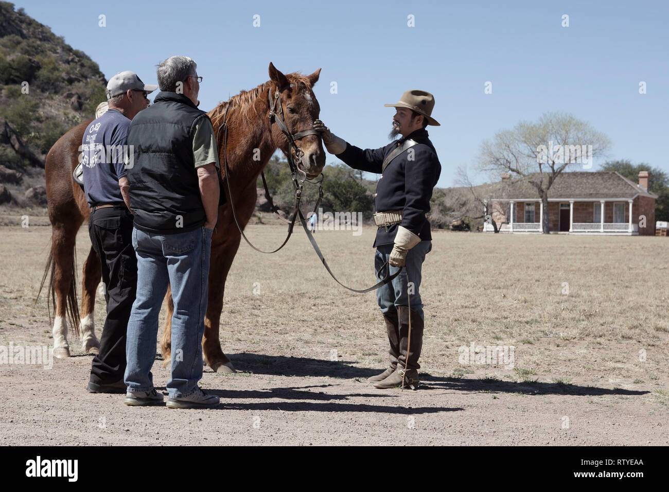 A Fort Davis National Historic Site, Texas, volunteer dressed as a trooper of the Eighth Regiment of Cavalry, answers visitors questions. - Stock Image