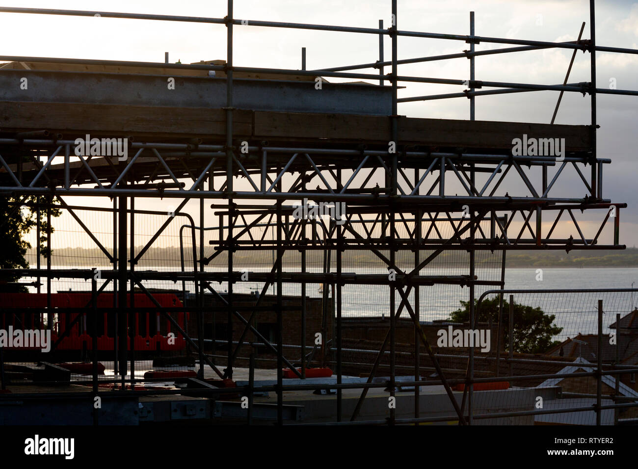 roof,wall,window,door, layer,joiner,roofer, painter,decorator, scaffolding, building, house, over,looking,sea, Cowes, Isle of Wight, England, UK, - Stock Image