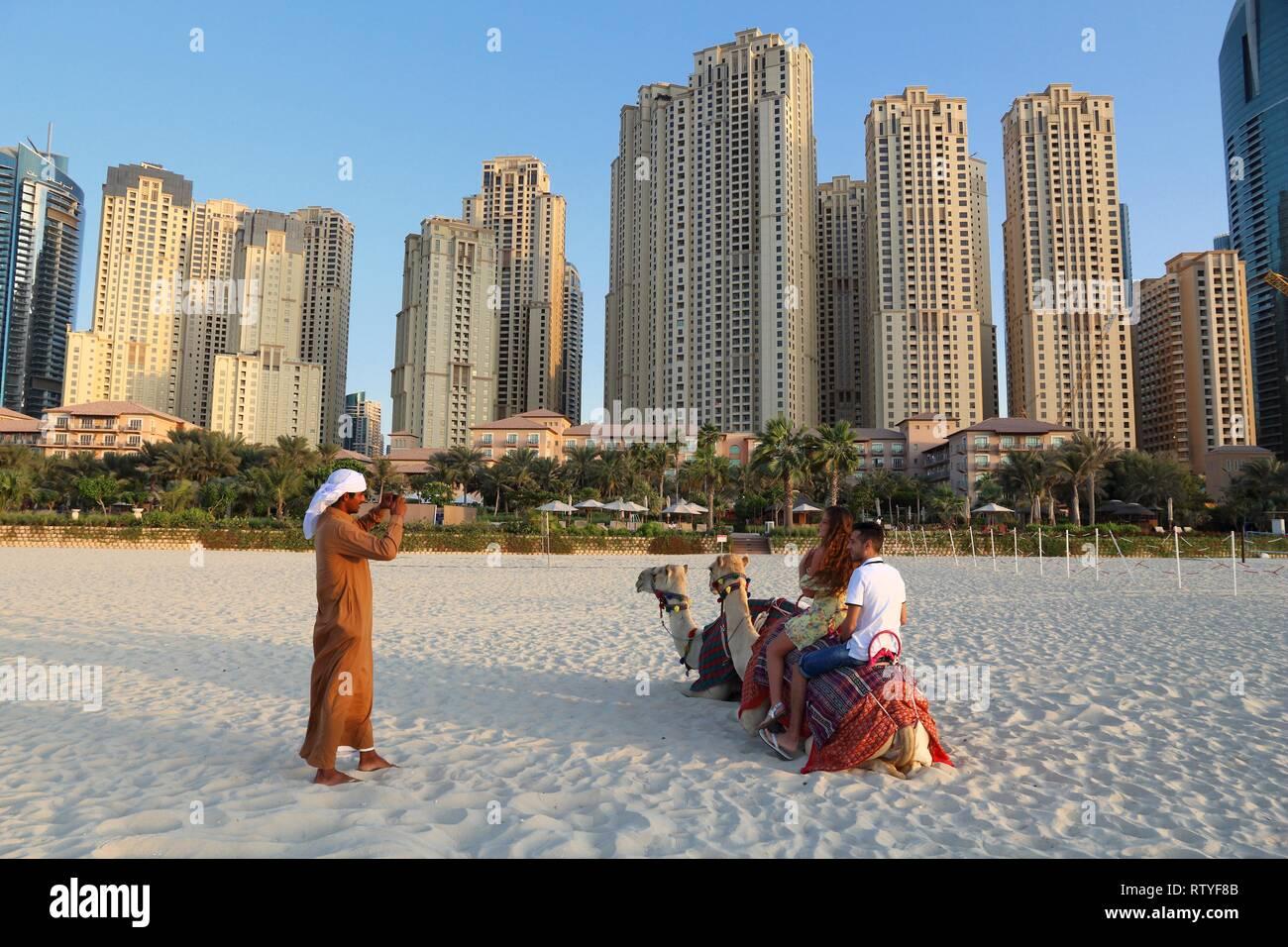 DUBAI, UAE - NOVEMBER 23, 2017: Tourists ride camels in front of Jumeirah Beach Residence in Dubai, United Arab Emirates. Dubai has 14.9 million annua - Stock Image