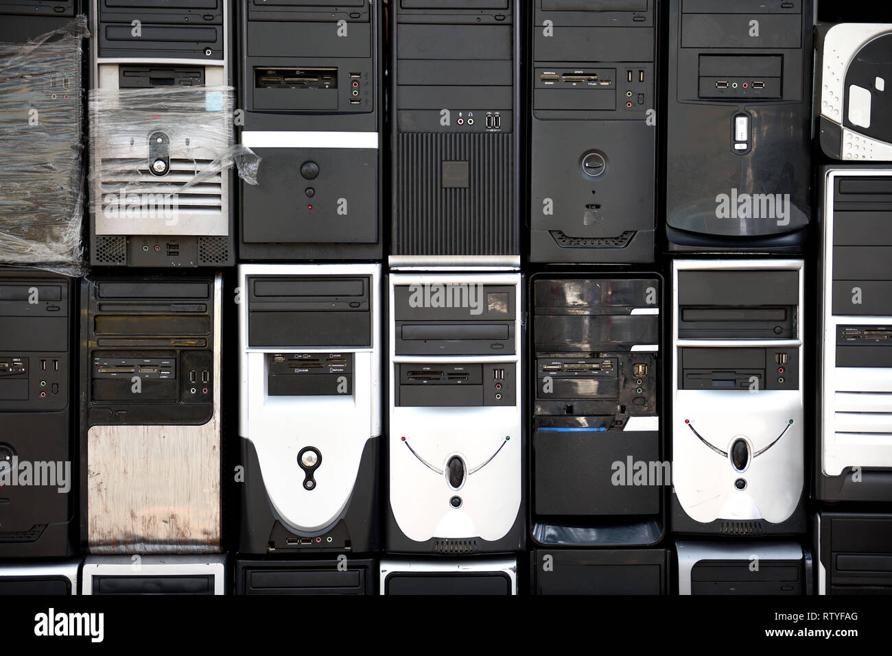 Rows of stacked, used, outdated desktop computer tower equipment, obsolete technology. - Stock Image