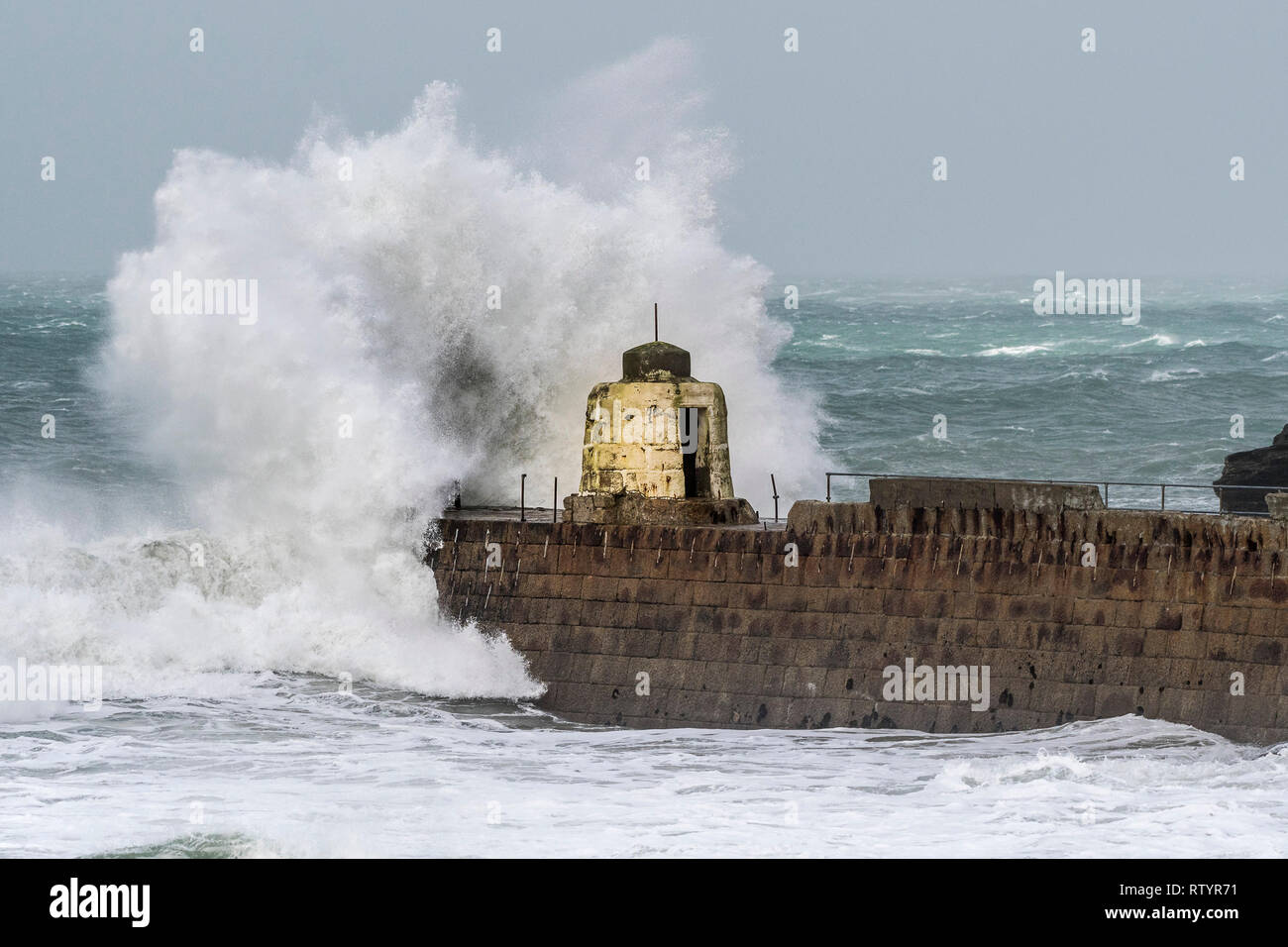 Portreath, Cornwall, UK. 3rd March, 2019.  Storm Freya swept into the Cornish coast.  The historic Monkey Hut on the pier at Portreath bravely withstood the high seas, driving wind and damaging waves.  Gordon Scammell/Alamy Live News. - Stock Image