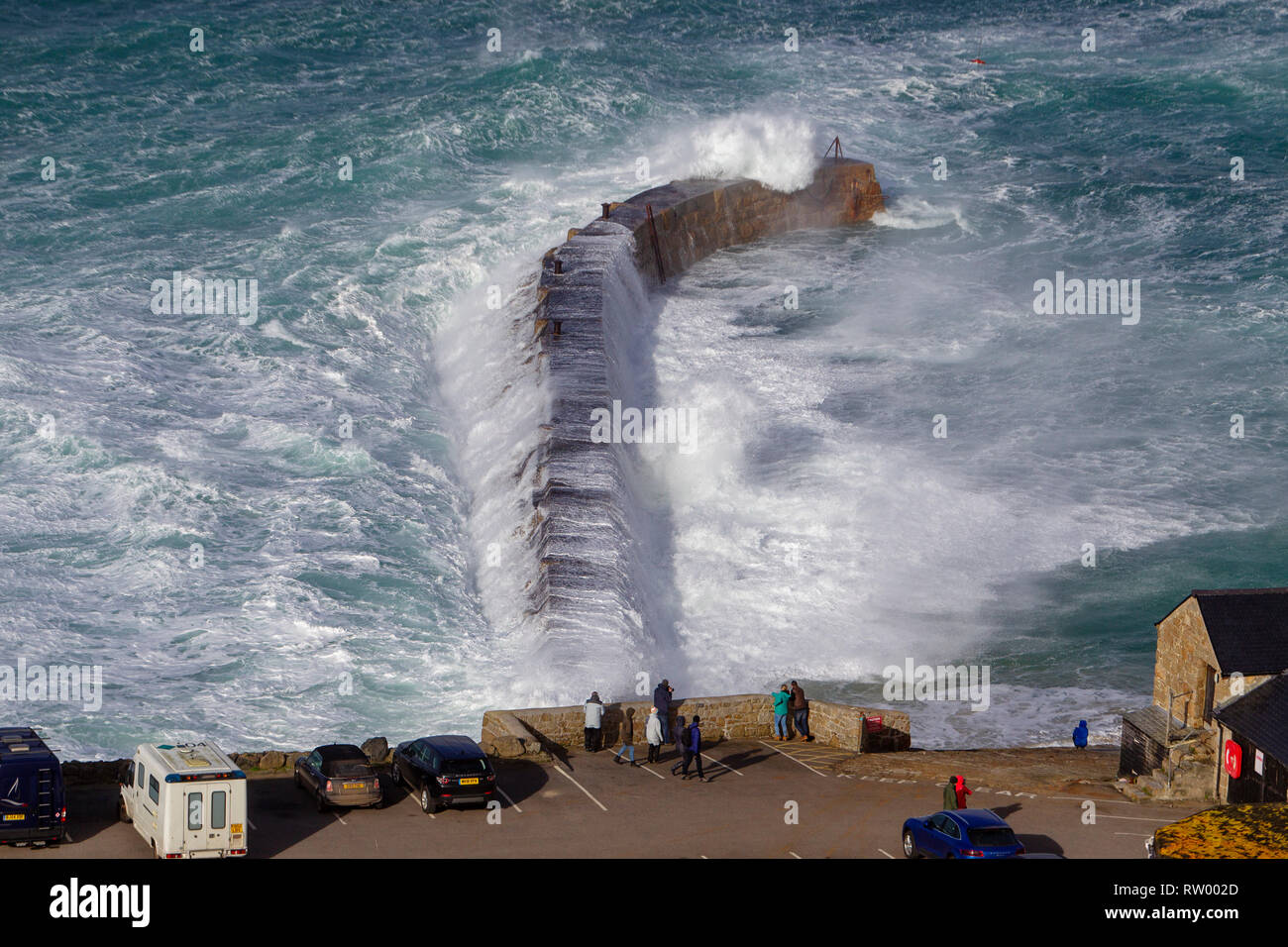 Sennen, Cornwall, UK. 3rd  March 2019. Gale force winds and 20ft high waves lash the granite cliffs of Cornwall. Daring jumpers get caught by some huge waves swamping the pier. Credit: Mike Newman/Alamy Live News. - Stock Image
