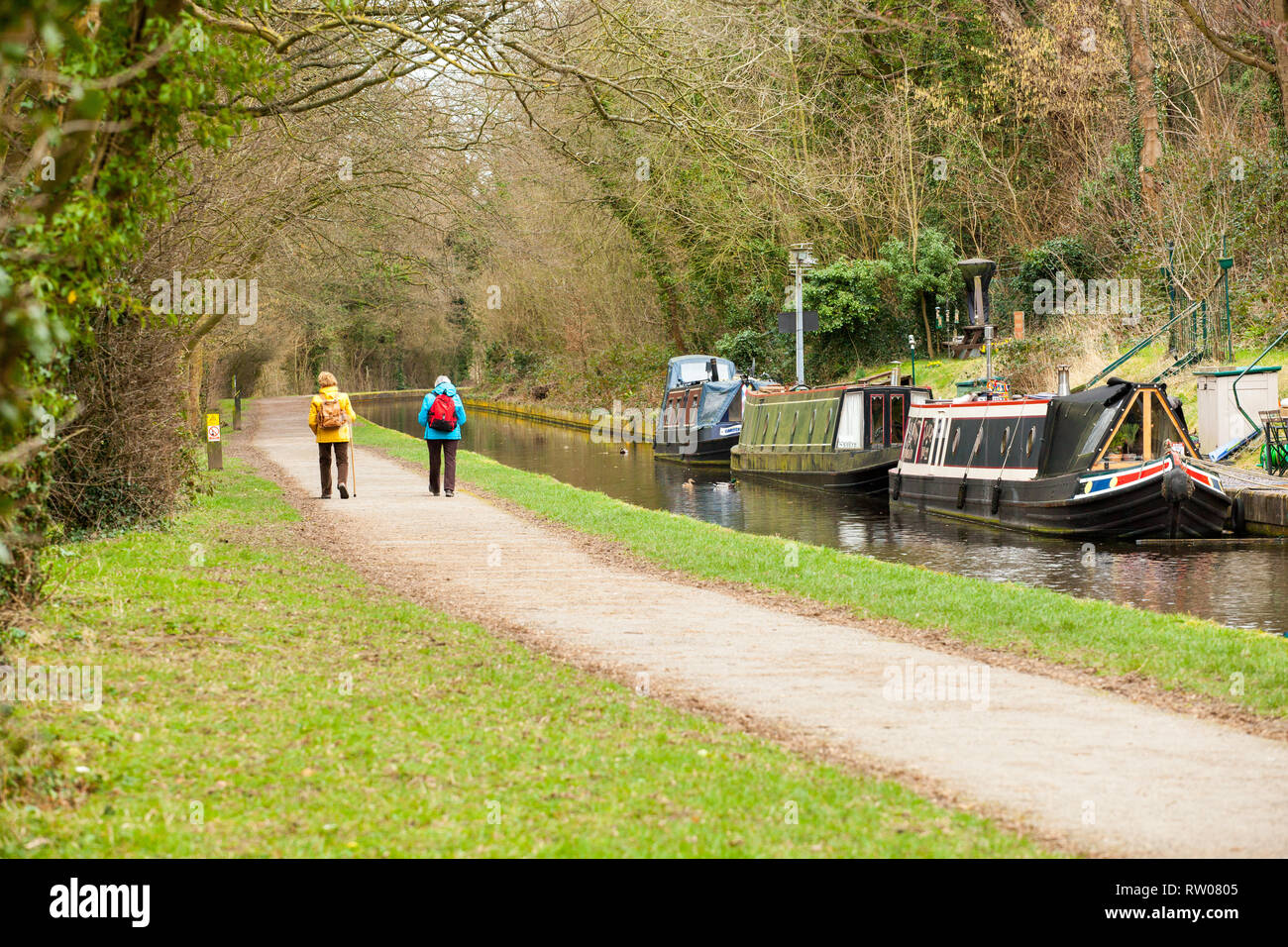 Two women wearing rucksacks backpacks walking along the Llangollen canal towpath near  Pontcysyllte North Wales UK with canal narrowboats moored - Stock Image