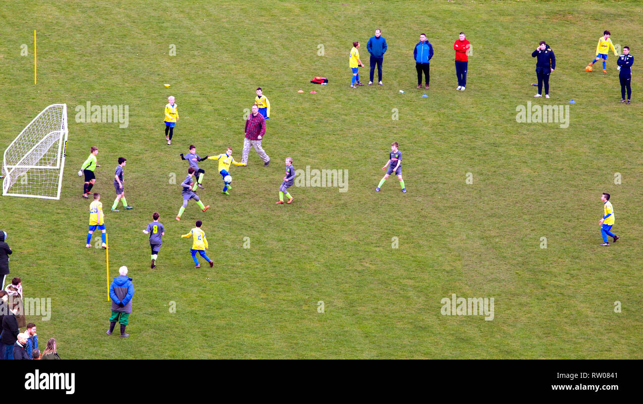 Schoolboys playing an amateur schoolboy sport football  match game Stock Photo