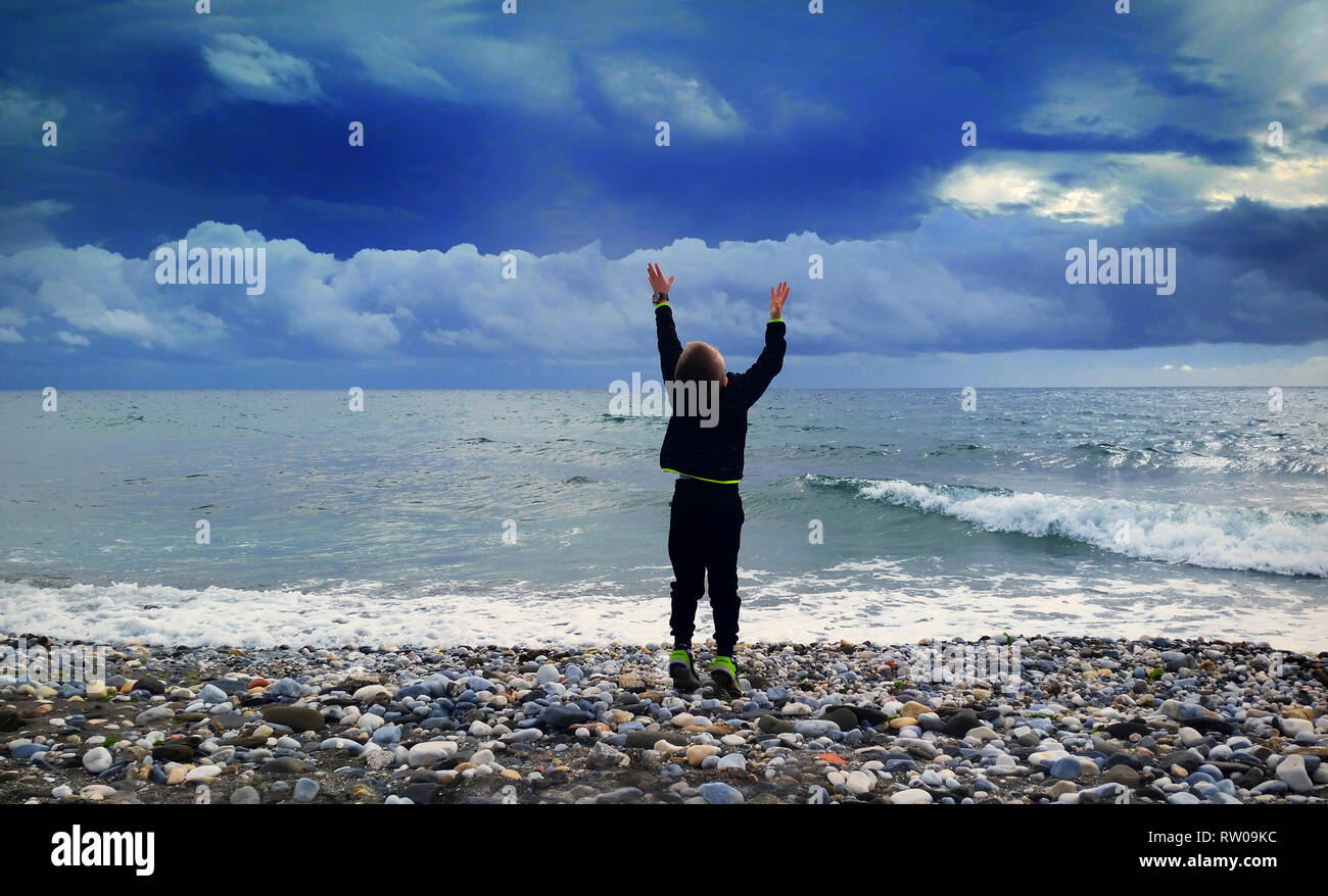 Young boy reaching for the sky, Torrox Costa Beach, Costa del Sol, Malaga Province, Andalucia, Spain. - Stock Image