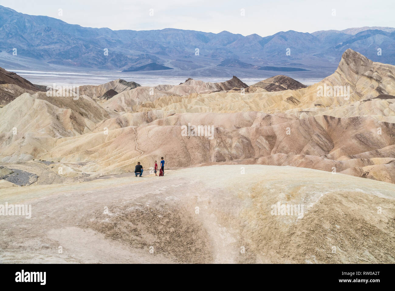 A view of Zabrinski Point in Death Valley, California with a father and his two children in the foreground. - Stock Image