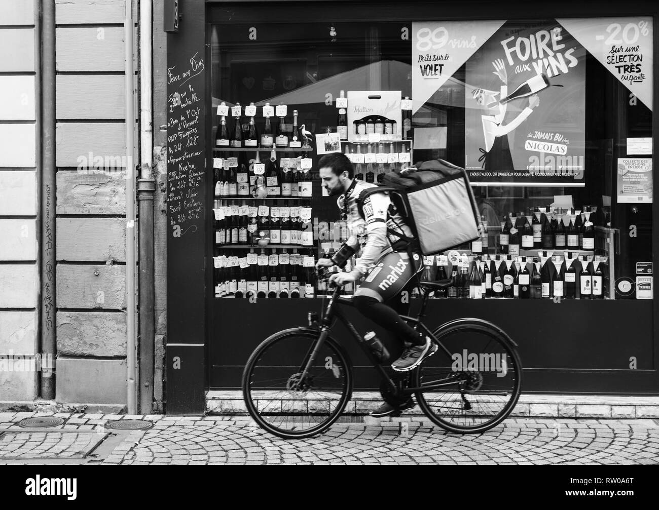 Strasbourg, France - Oct 1, 2017: Blacck and white image of Deliveroo biker wearing cycling branded outfit.  The online food delivery company was founded in 2013 by Will Shu and Greg Orlowski - Stock Image