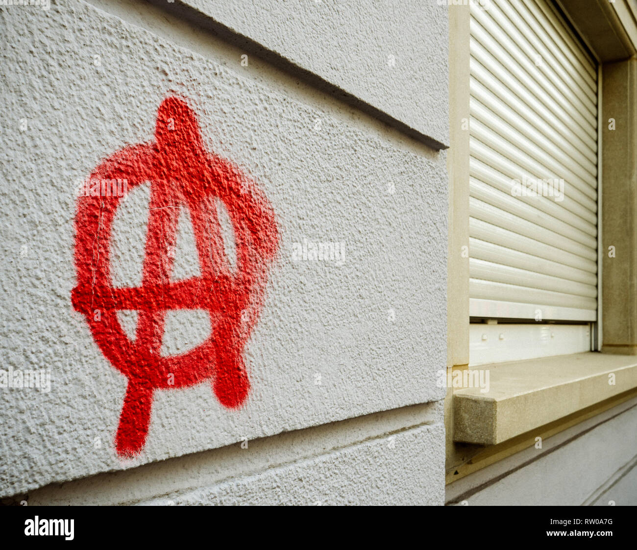 Anarchy graffiti on wall painted with red paint - Stock Image