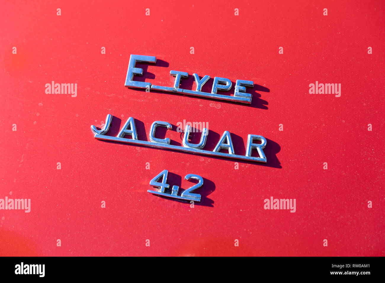 E Type Jaguar 4.2 , chrome letters on red background - Stock Image
