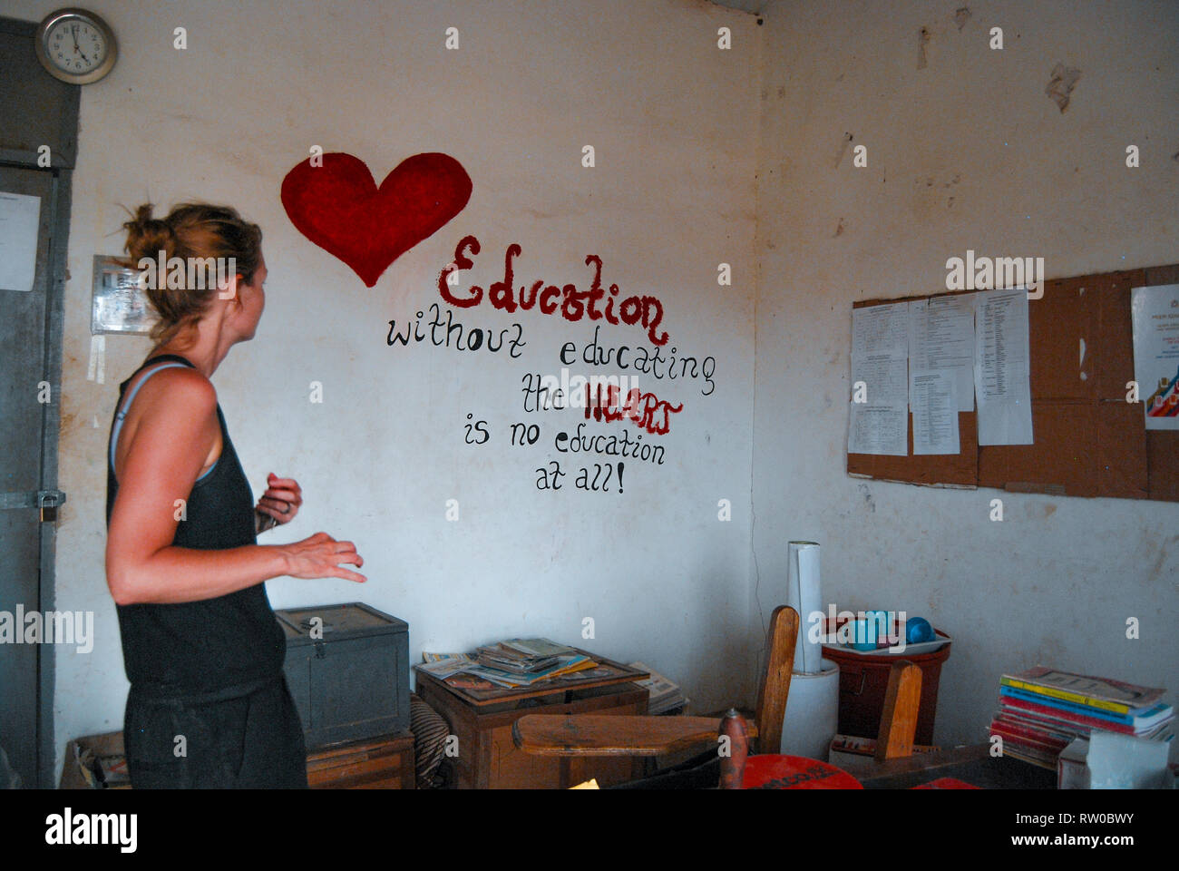 A caucasian woman standing on a local school office of a Ghanaian school. There is a beautiful heart and a message painted on the wall - Stock Image