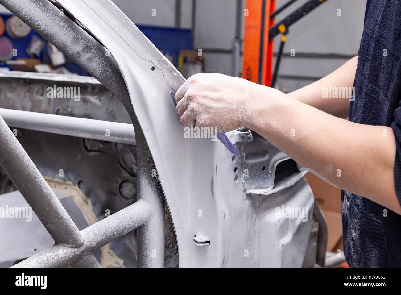 The body repairman grinds the white car's frame with purple emery paper in preparation for painting after applying putty in a vehicle repair workshop  - Stock Image