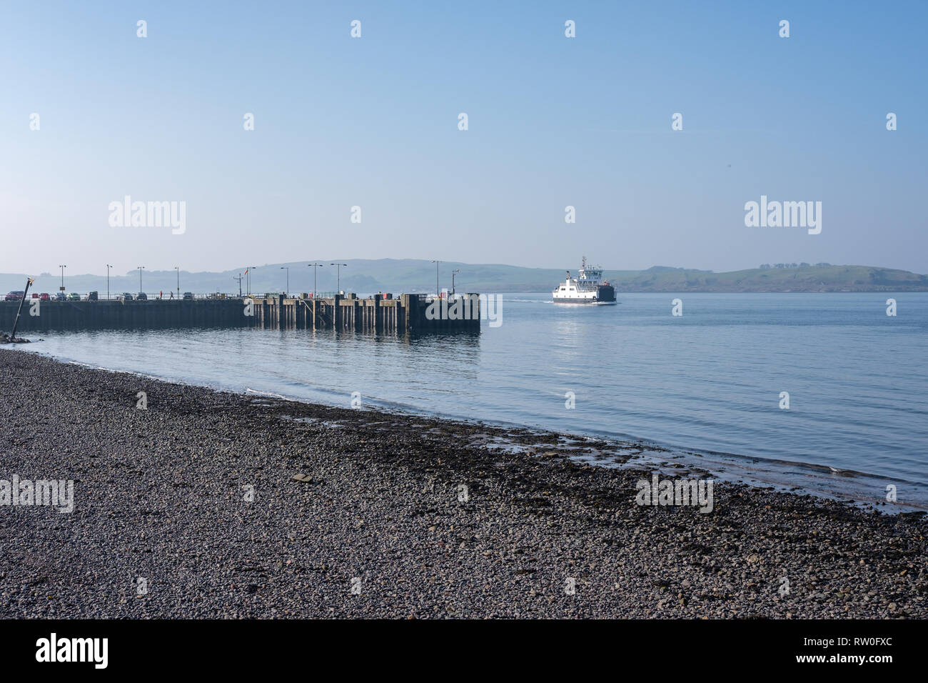 Largs Pier and Millport Ferry on a beautiful February day in Scotland with blue sky and a blue River Clyde. - Stock Image