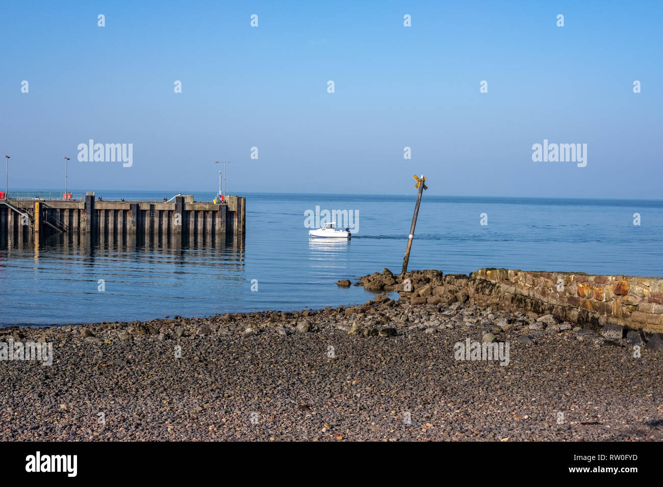 Unusually warm February weather for Largs Pier and a small white boat on the West coast of Scotland with bright blue sky and temperature of 16 °C. - Stock Image
