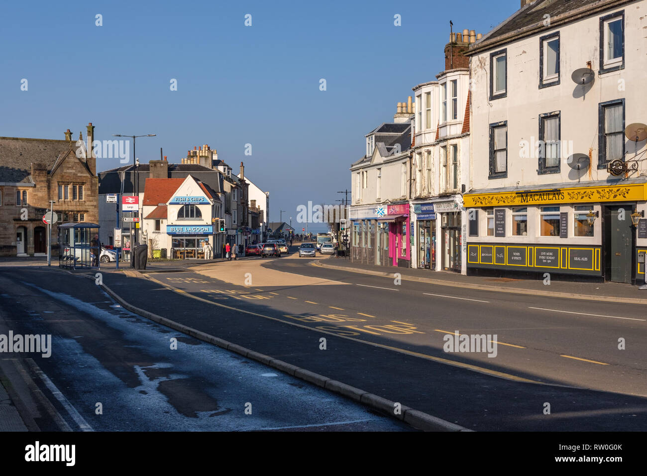 Largs, Scotland, UK - February 27, 2019: Unusually warm February weather for Largs Main Street on the West coast of Scotland with bright blue sky and  - Stock Image