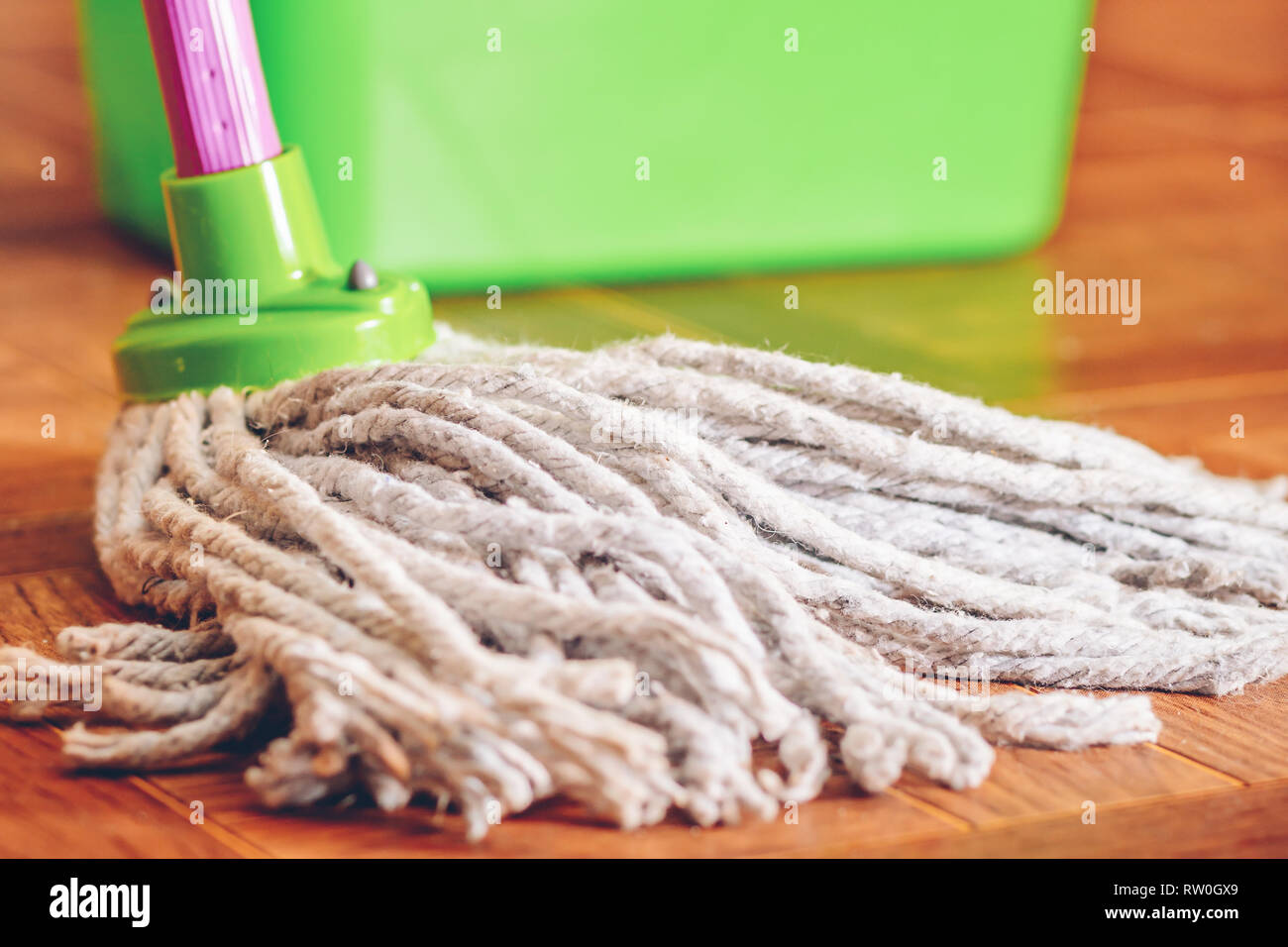 Rope mop for cleaning the floor on the background of a plastic bucket Stock Photo