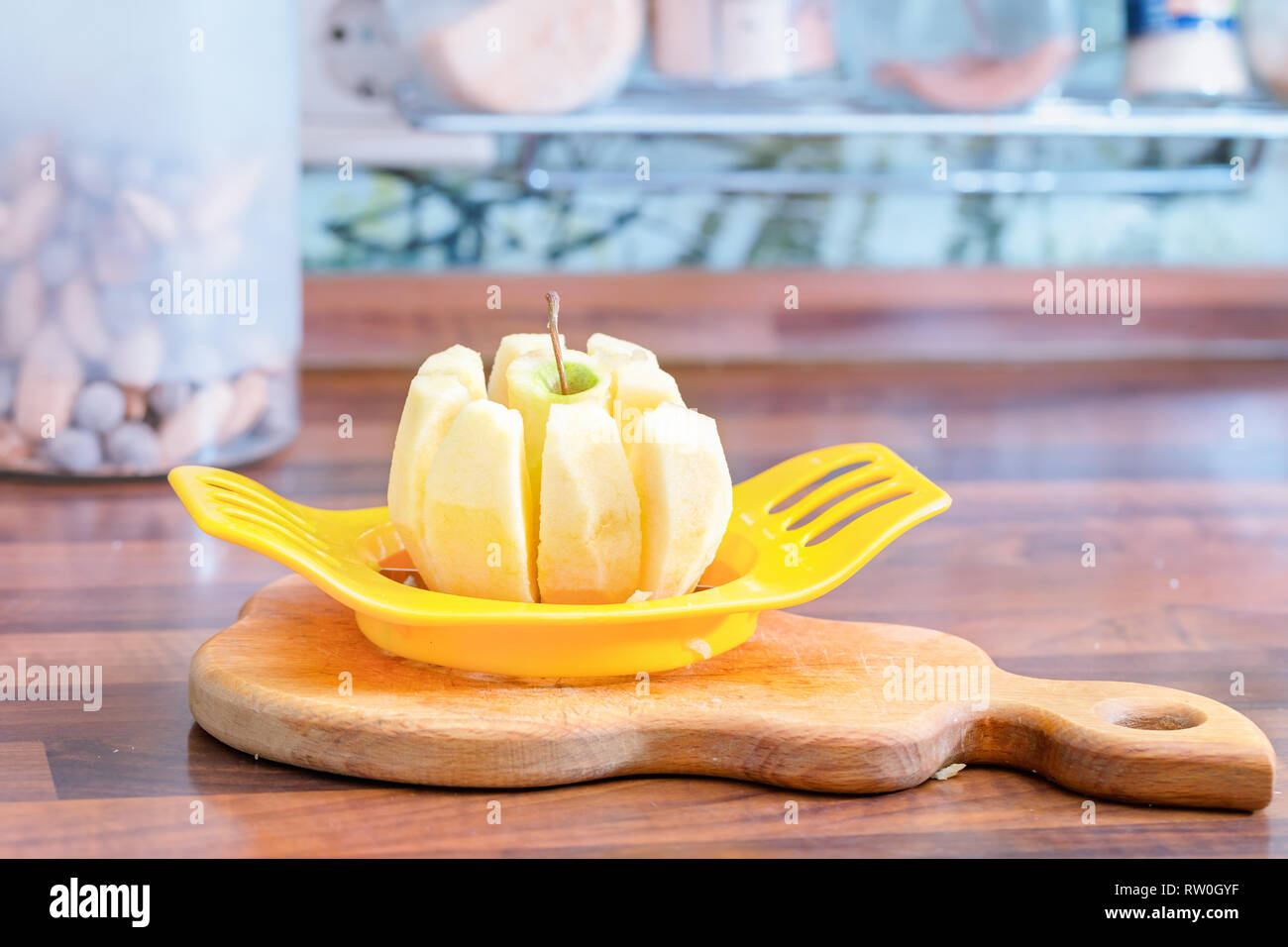 Cutting the apple into slices with a special device. - Stock Image