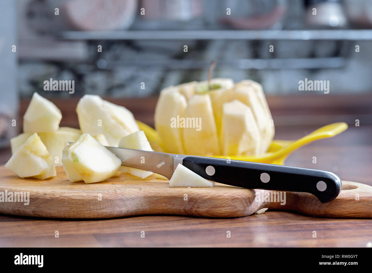 Slices of peeled apple and a knife on a cutting board. - Stock Image