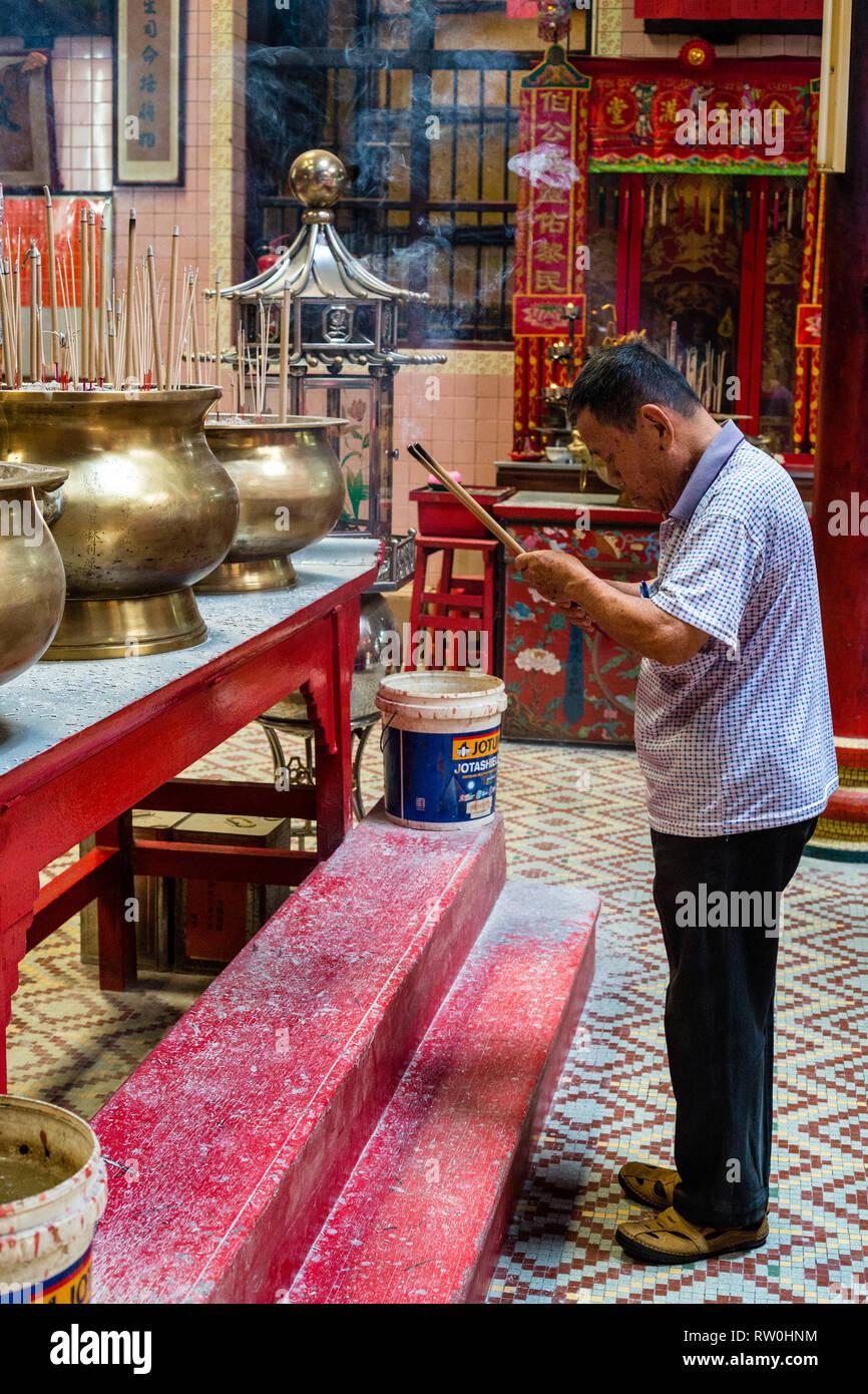 Sin Sze Si Ya Taoist Temple, Chinatown, Kuala Lumpur, Malaysia.  Worshiper Bowing with Joss Sticks.  Oldest Taoist temple in Kuala Lumpur (1864). - Stock Image