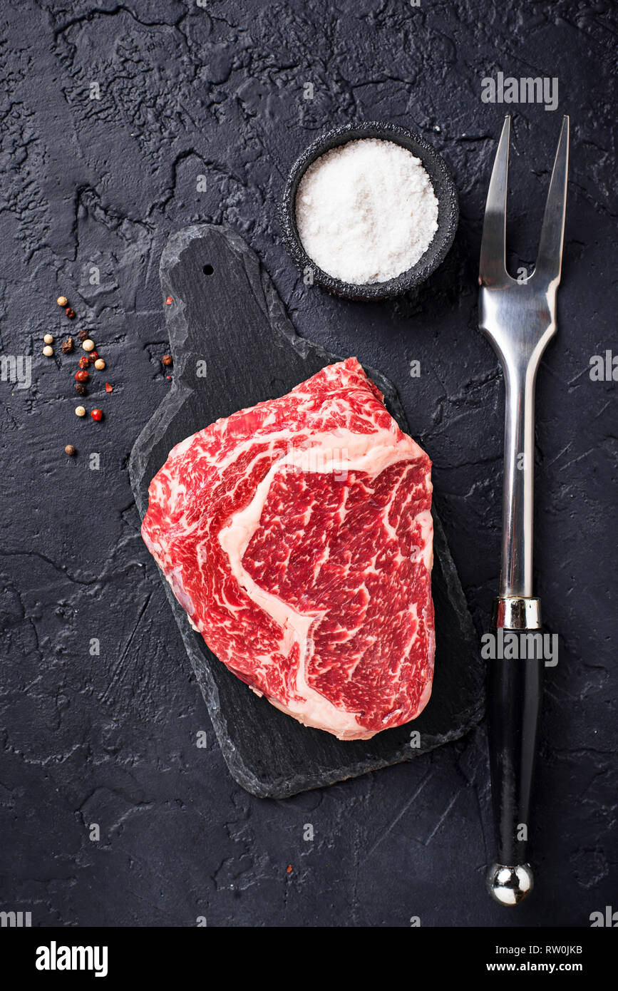 Raw marbled ribeye steak and spices - Stock Image