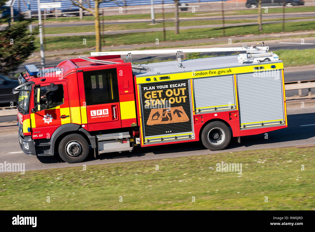 London Fire Brigade fire engine, fire tender driving on the road. Mercedes Benz Atego 1327. Plan your escape, get out stay out - Stock Image