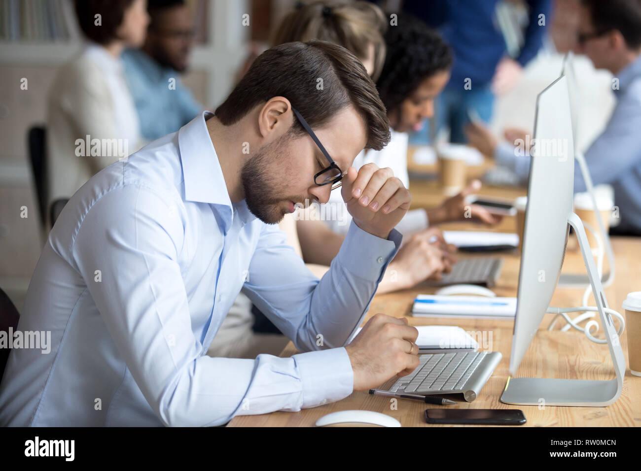 Businessman feels desperate having serious problem at work - Stock Image