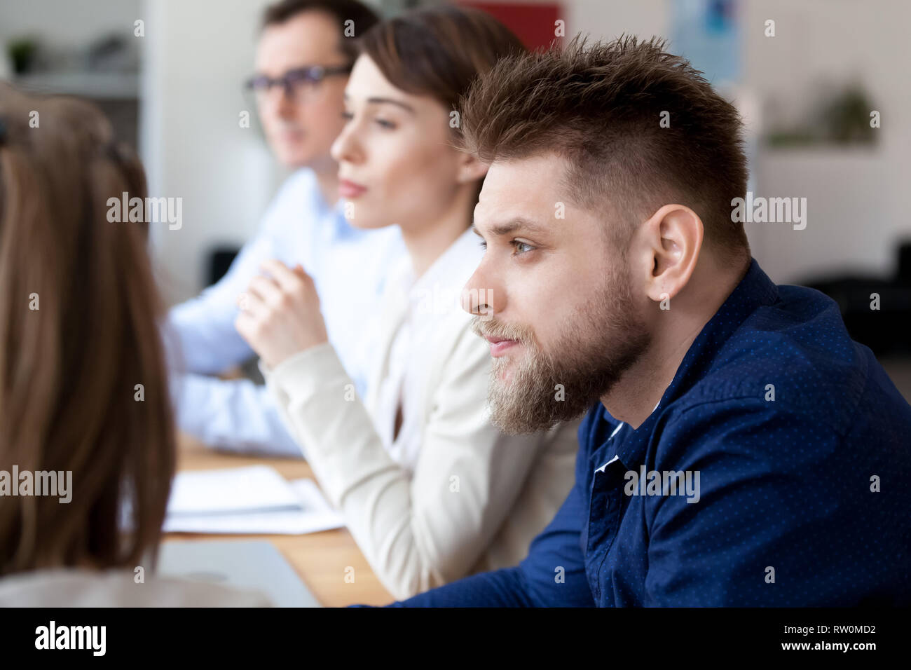 Concentrated millennial employee sitting at business meeting - Stock Image