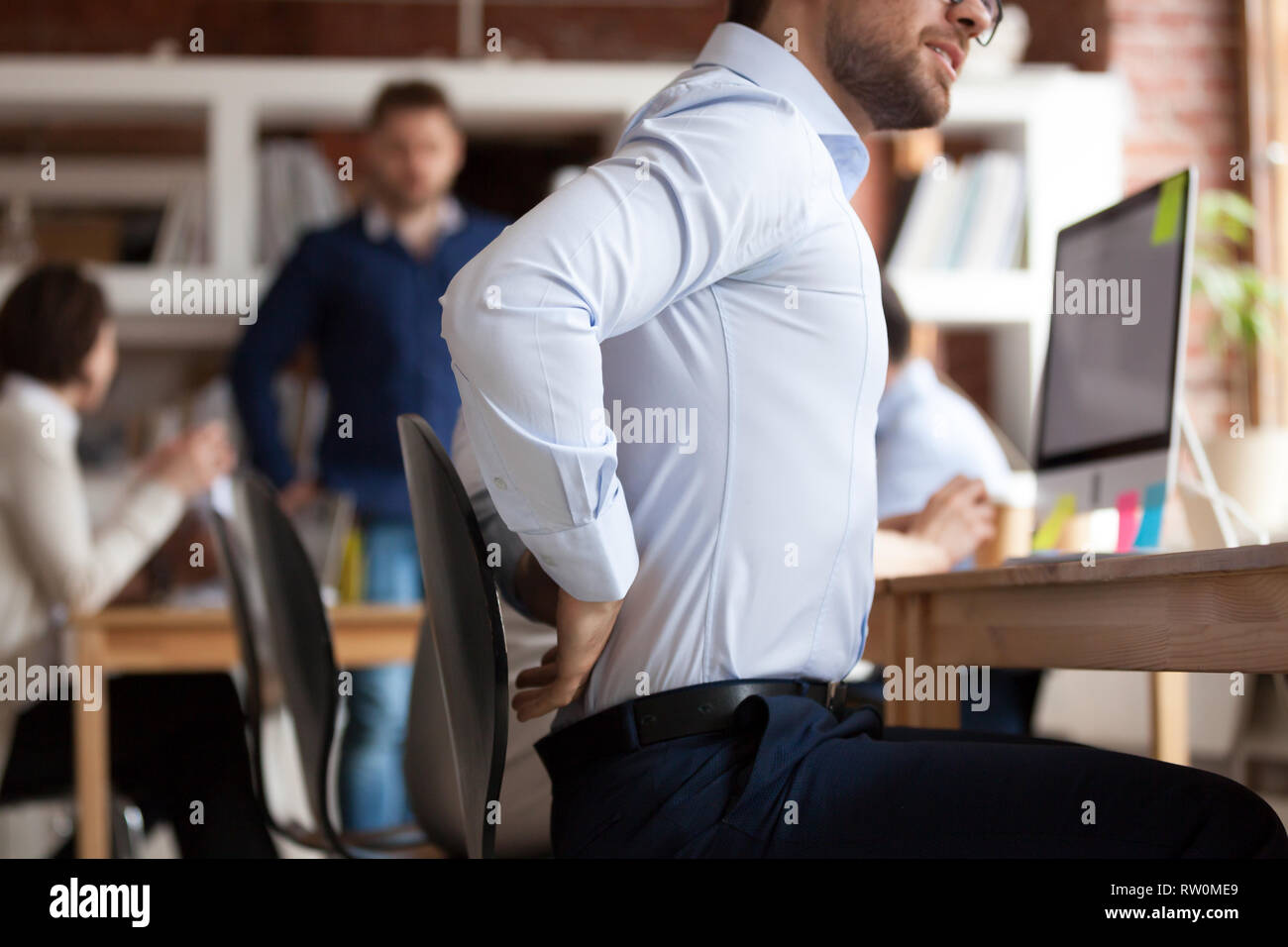 Businessman suffers from lower back pain sitting in shared office - Stock Image