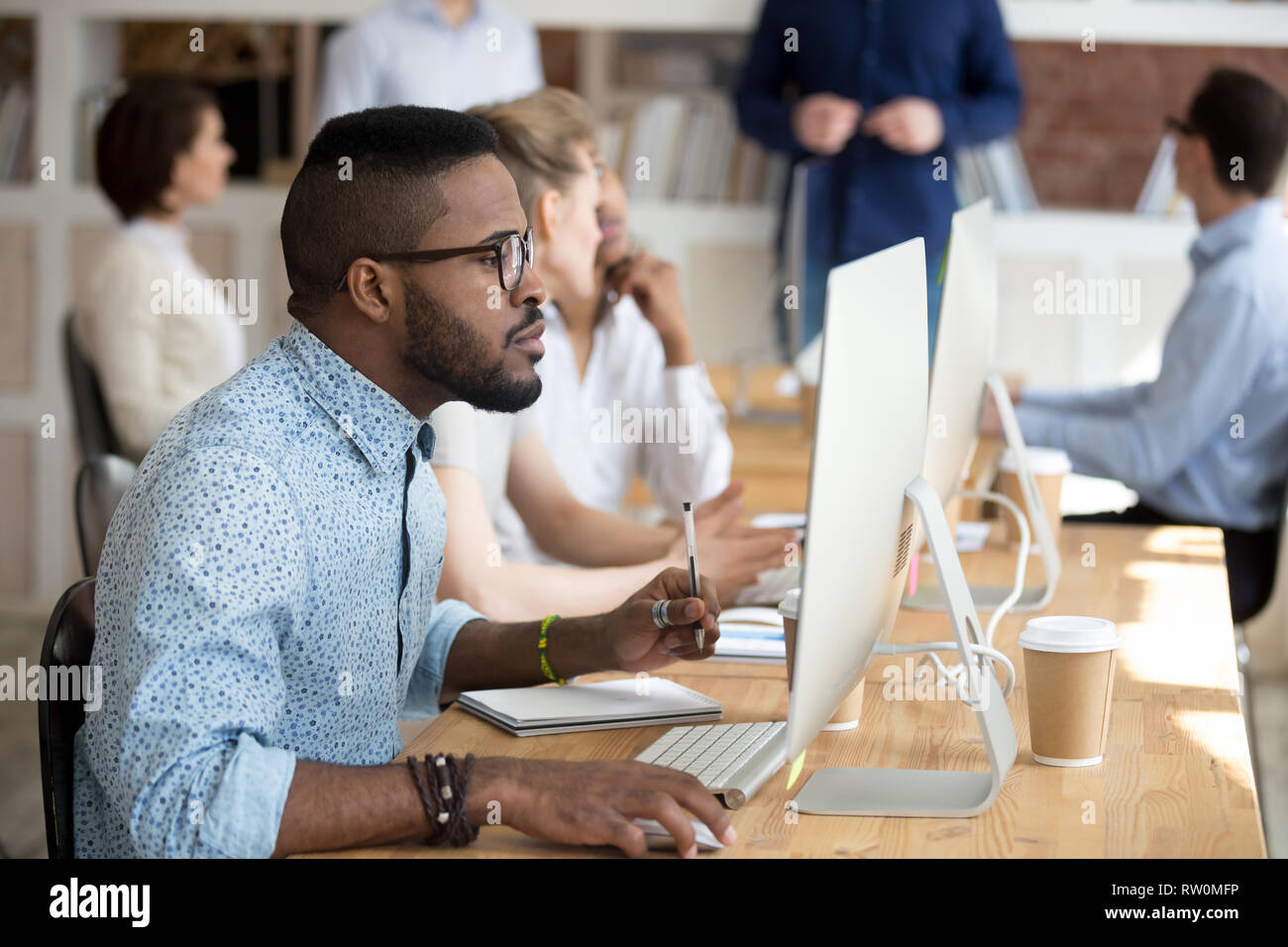 Black manager holding pen make notes on textbook using pc - Stock Image