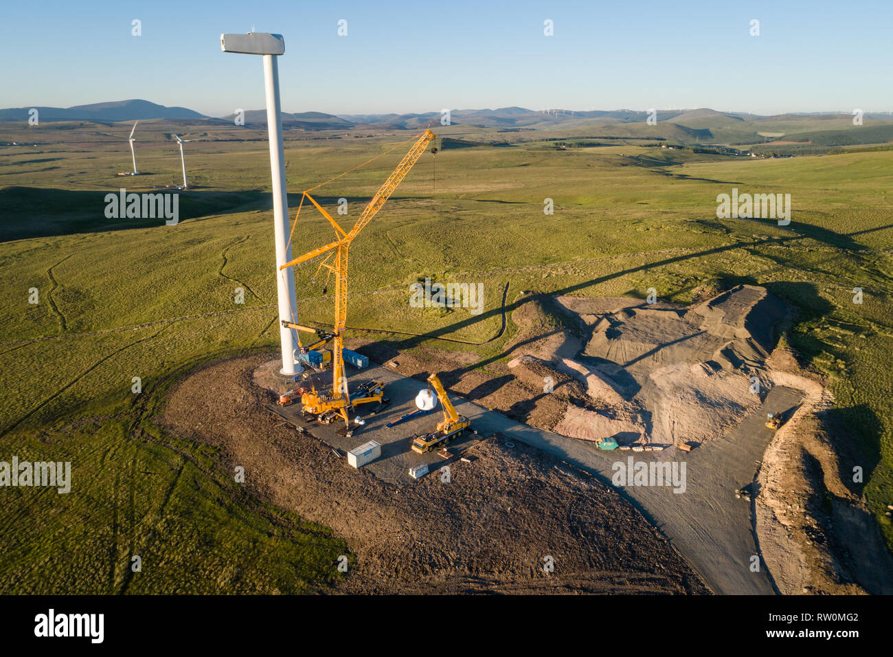 Aerial image showing construction of wind turbines using cranes at Andershaw Wind Farm near Douglas in South Lanarkshire, Southern Scotland. - Stock Image