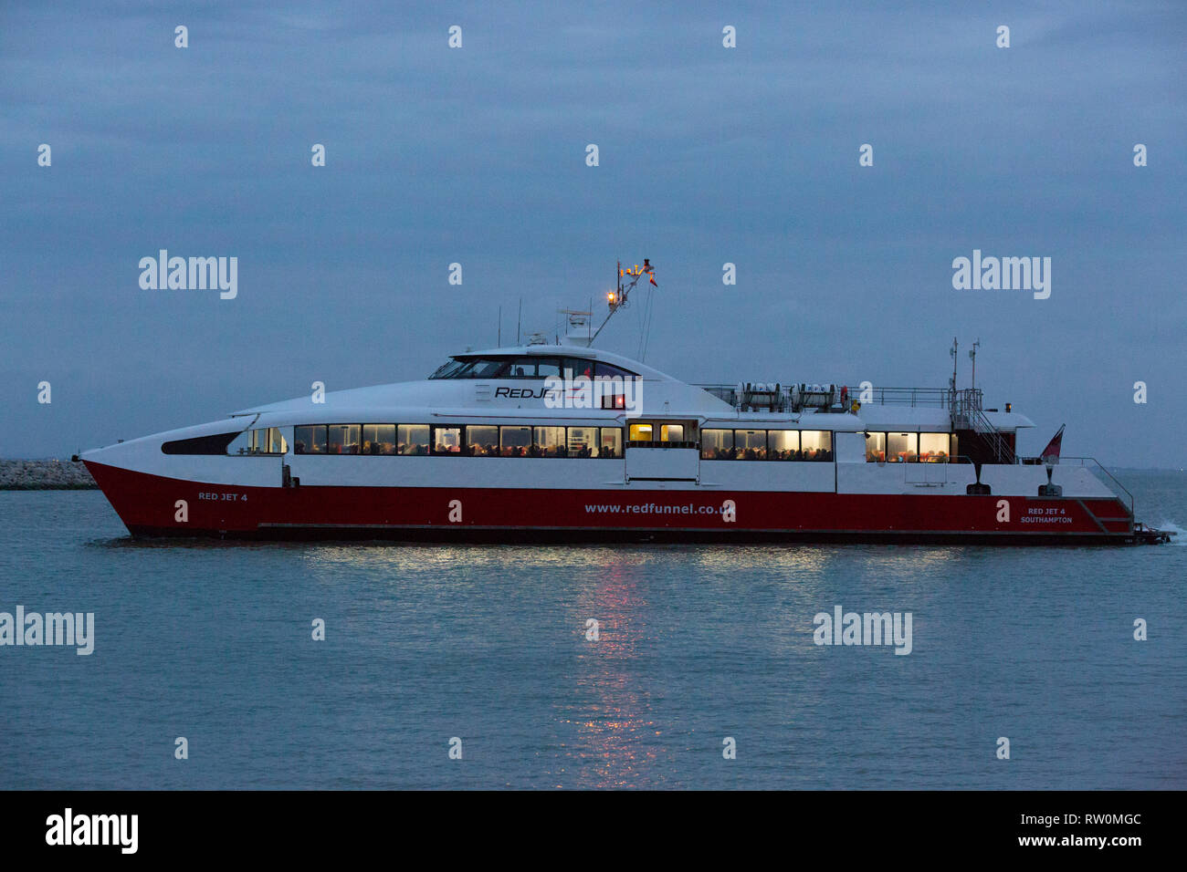 Passenger,ferry, Red,Funnel,Jet,4, Cowes,Southampton,fast,dusk,commute,commuter,Isle of Wight,England,UK, - Stock Image
