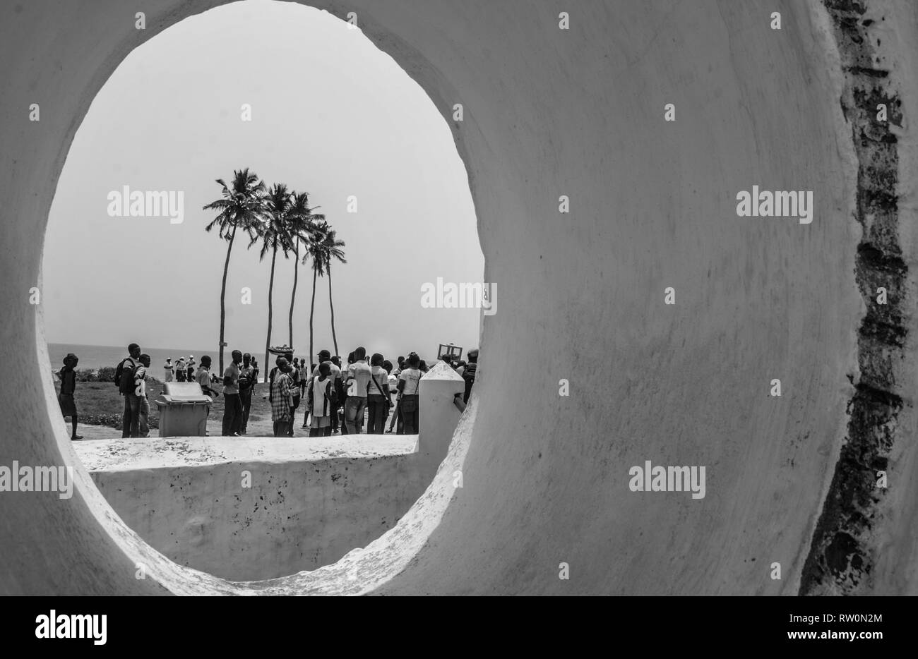 A view to the beach thorough the window of the St George of the MIne. Gathering crowd on the background of palm trees can be seen. Black and white. - Stock Image