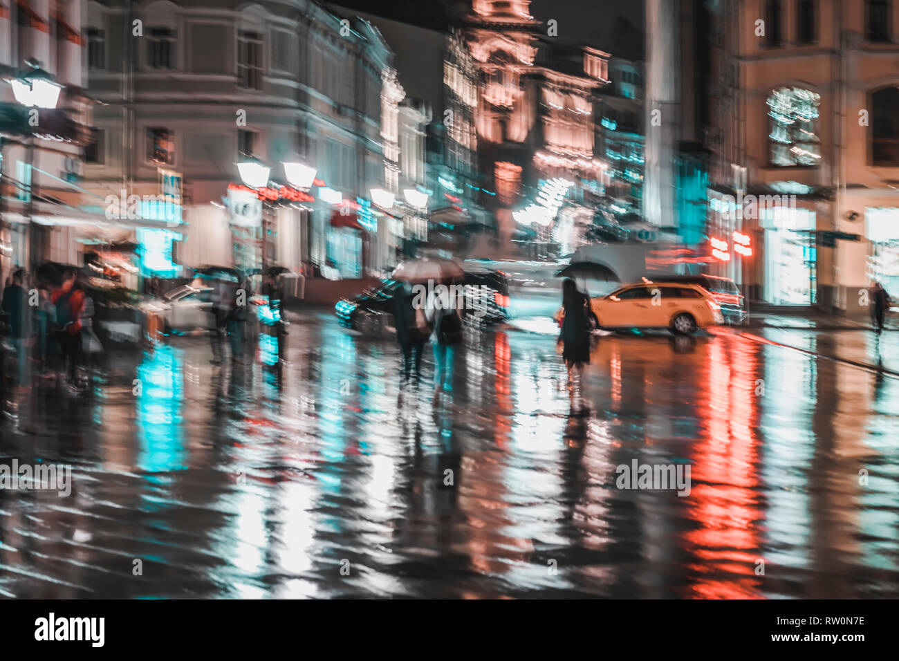 City street in rainy night, Abstract bright blurred background with unidentified people. Vivid illumination, reflection in wet pavement of shop - Stock Image
