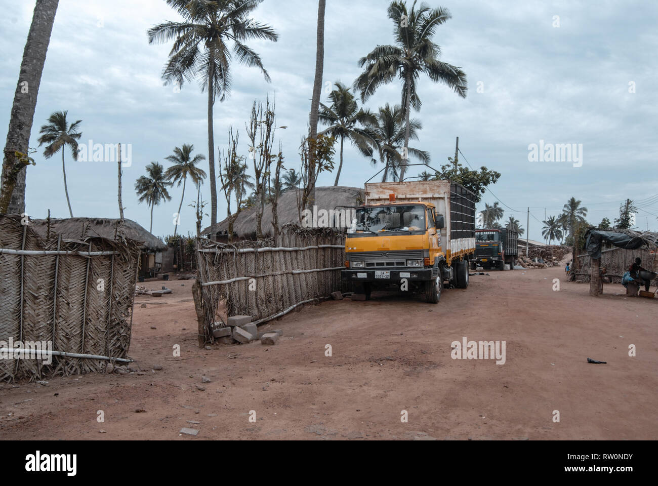 A yellow truck parked at a street of a suburb of tropical town of Elmina, Ghana - Stock Image